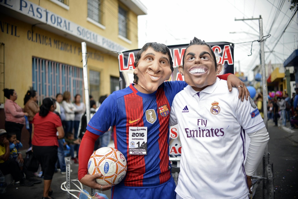 Revelers dressed as Argentinian football player Lionel Messi and Portuguese player Cristiano Ronaldo take part in the traditional