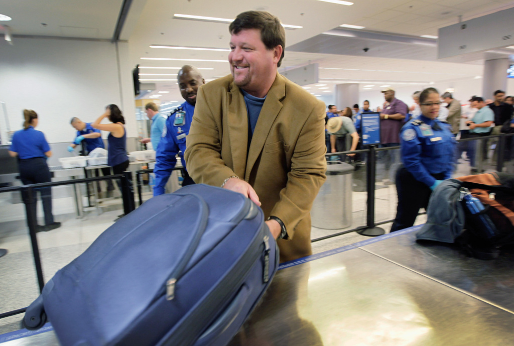 Ben Starrett places his bag on the table for security screening as he uses the new TSA PreCheck lane being implemented by the Transportation Security Administration at Miami International Airport on October 4, 2011.