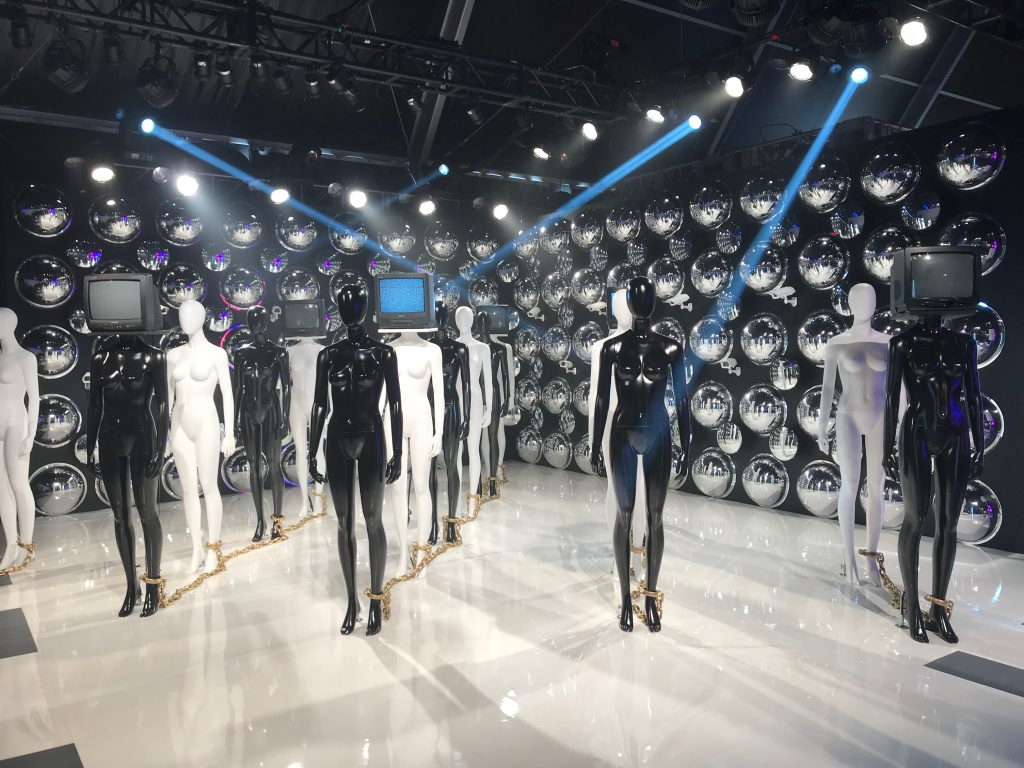 The What's Your Frequency room is a collaboration with Janelle Monáe, where visitors are filmed while they explore the room and their images are displayed on mannequins with TV heads. She hopes it will push people to contemplate surveillance, technology, media and conformity.