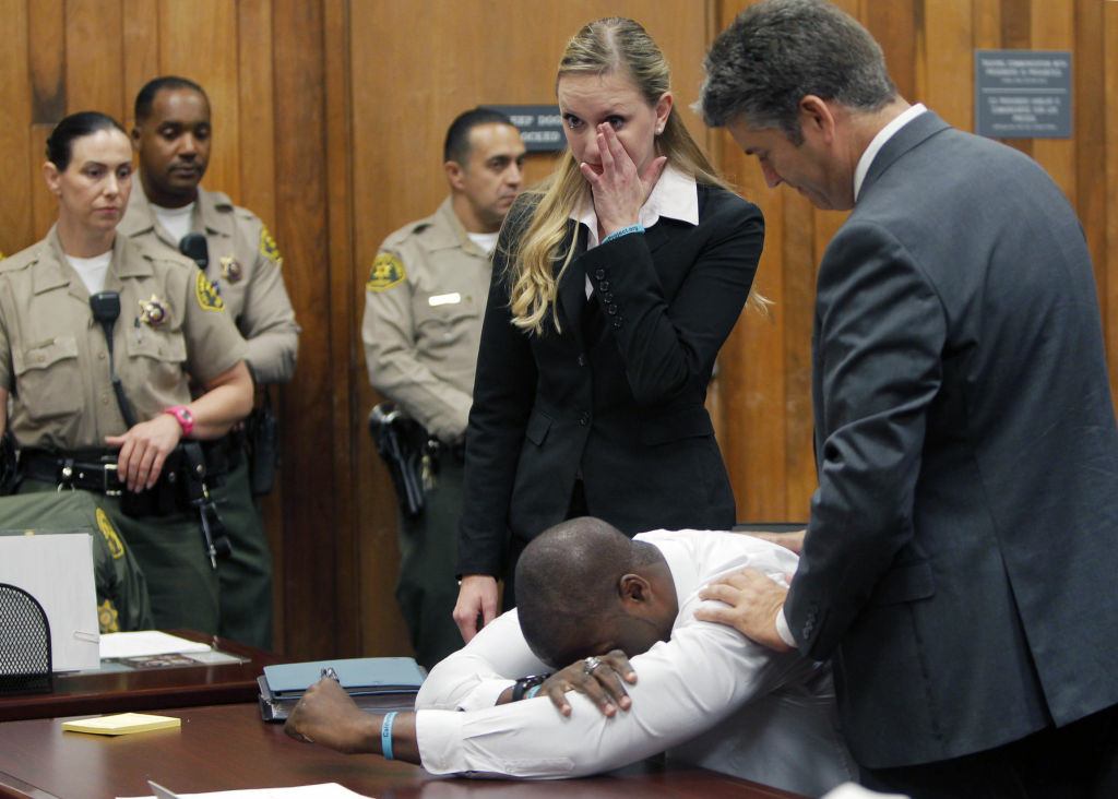 Brian Banks becomes emotional as his attorney Justin Brooks, right, and attorney Alissa Bjerkhoel stand by, as Banks' rape conviction is dismissed Thursday, May 24, 2012, in Long Beach, Calif. It has been 10 years since Banks, then 16, pleaded no contest to a rape charge brought after a childhood friend falsely accused him of attacking her on their high school campus, shattering his dreams of a pro career.