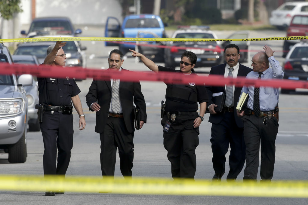 Law enforcement members look over the scene of an officer involved shooting in Torrance, Calif. Thursday, Feb. 7, 2013. Thousands of police officers throughout Southern California and Nevada hunted for a former Los Angeles officer, Christopher Dorner, who was angry over his firing and began a deadly shooting rampage that he warned in an online posting would target those on the force who wronged him, authorities said.