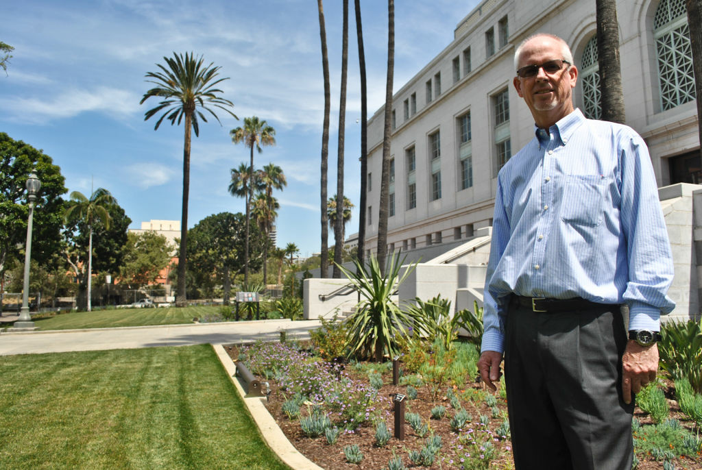 Thomas Gibson stands next to the garden he designed in the City Hall Lawn park. The park is now home to many plants that are native to California.