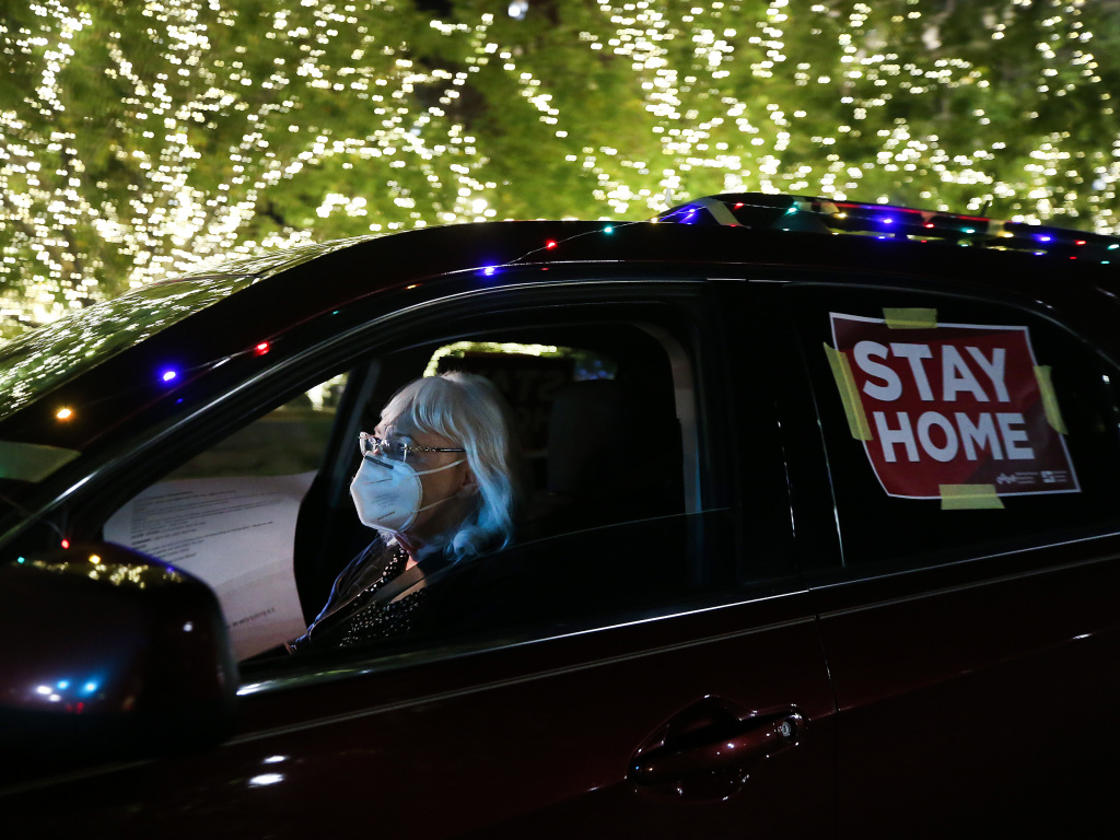 A 'Stay Home' sign is taped to a driver's vehicle as she passes Christmas lights during a car caravan of nurses calling for people to remain home amid a surge of COVID-19 cases in El Paso on November 16, 2020.