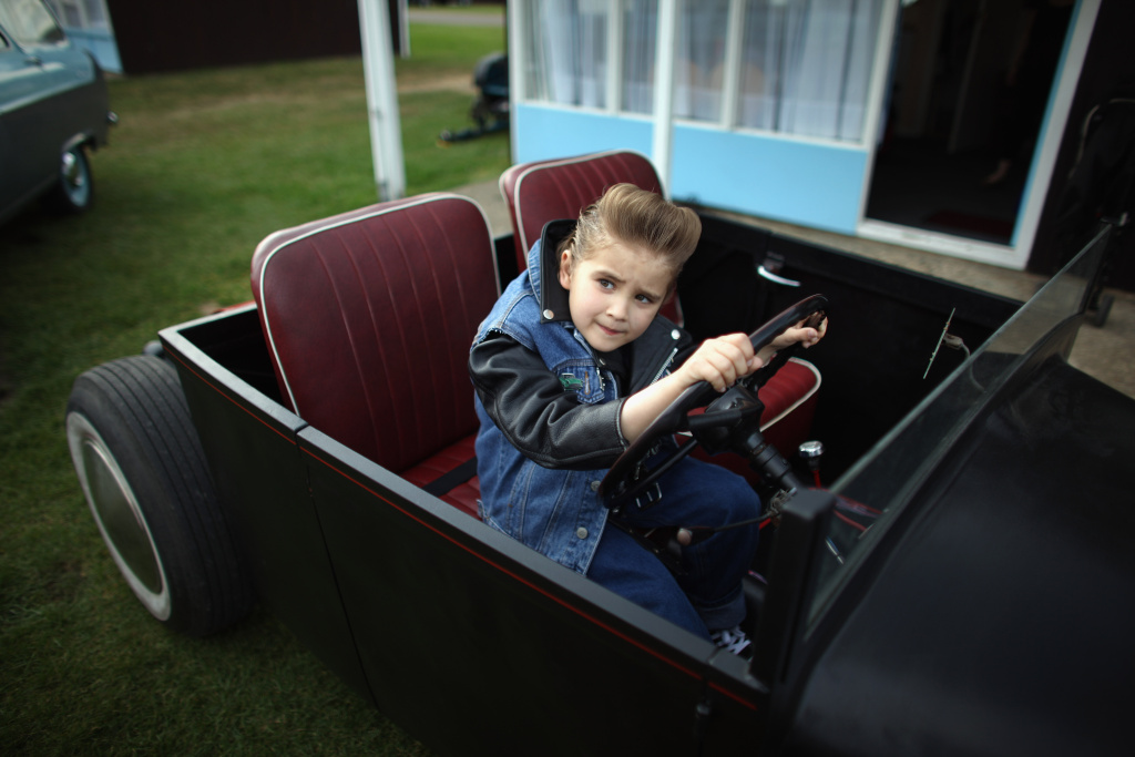 Buddy Monger, 8, plays in his father's hot rod during the Hemsby Rock n Roll Weekender in Hemsby, England on May 15, 2011.