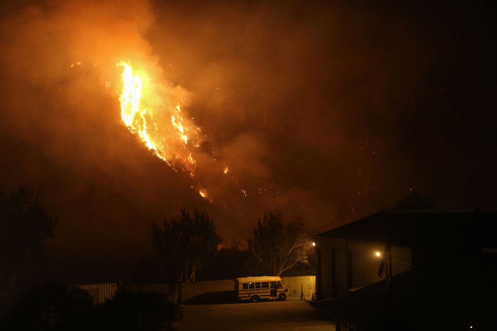 The Thomas Fire burns near a school bus on December 7, 2017 in Ventura, California.