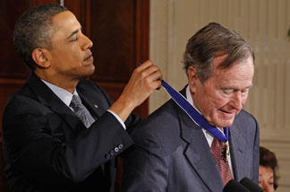 President Barack Obama (L) presents former U.S. President George H.W. Bush with the 2010 Medal of Freedom in the East Room of the White House February 15, 2011 in Washington, D.C. Obama presented the medal to twelve pioneers in sports, labor, politics and arts.