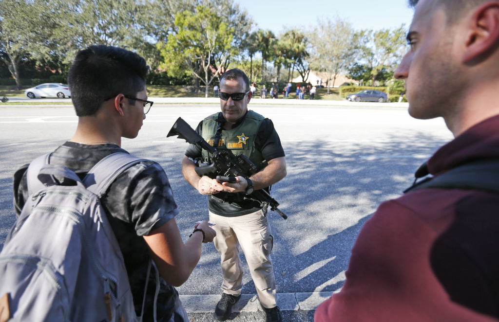 A law enforcement officer talks with students, Wednesday, Feb. 14, 2018, in Parkland, Fla. A shooting at Marjory Stoneman Douglas High School sent students rushing into the streets as SWAT team members swarmed in and locked down the building. Police were warning that the shooter was still at large even as ambulances converged on the scene and emergency workers appeared to be treating those possibly wounded.