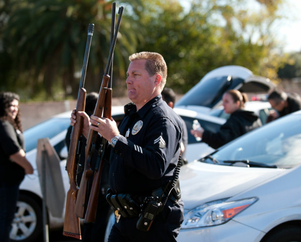Sgt. Ishmail removes a rifle from a gun owner's car on Wednesday morning at the Van Nuys Masonic Temple during a gun buyback event put on by the LAPD. Gun owners exchanged their firearms for grocery store gift cards.