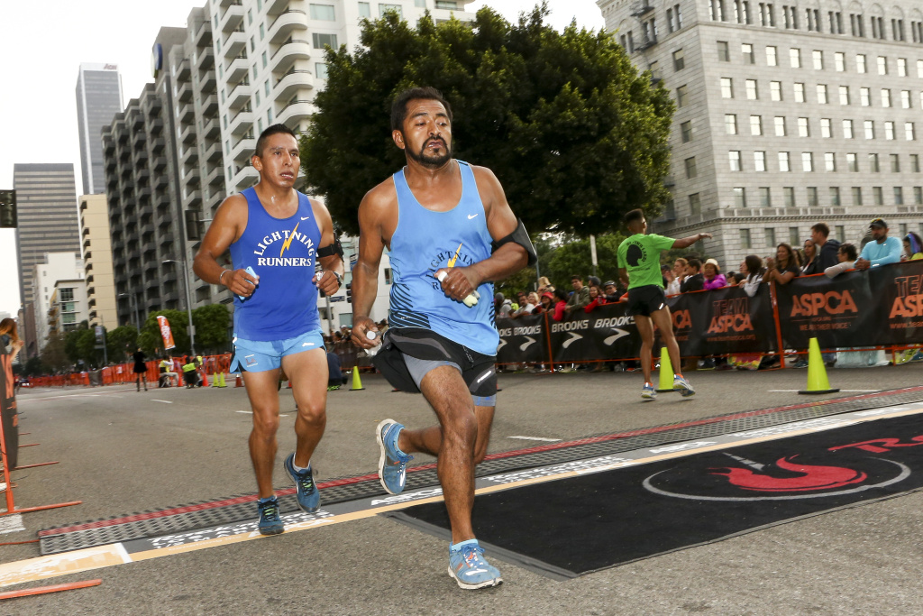 Runners prepare to cross the finish line at the Rock 'n' Roll Los Angeles Halloween Half-Marathon and 5K on October 26, 2014 in Los Angeles, California.