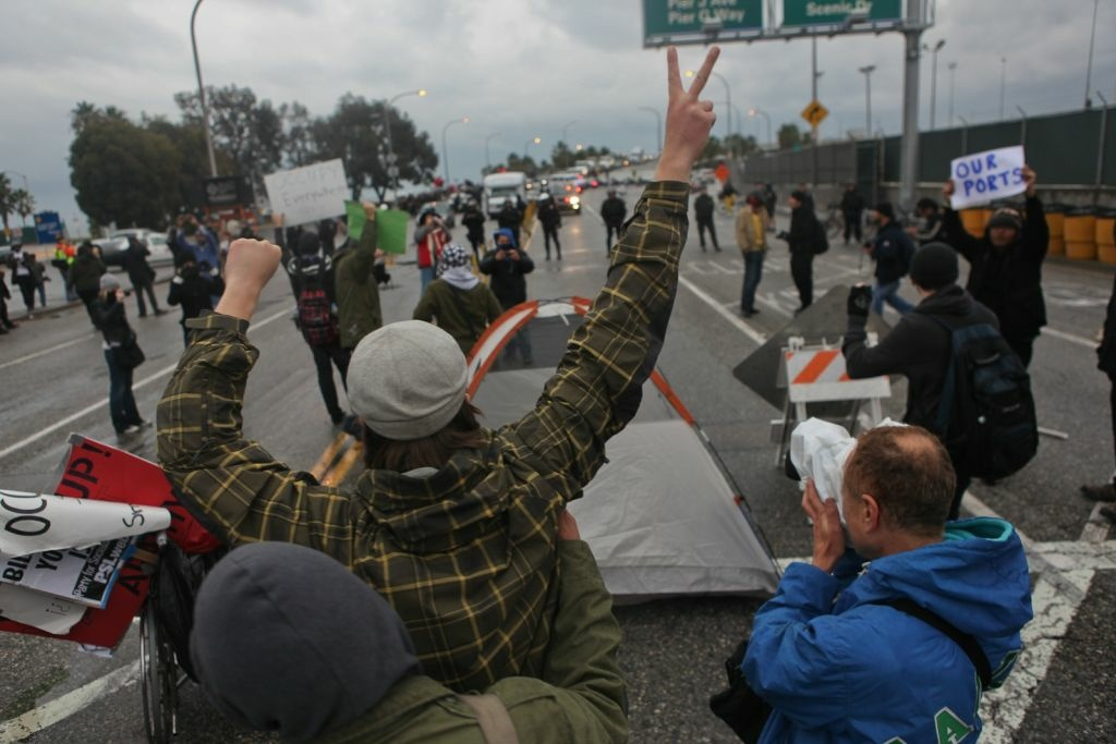 An Occupy protester shouts at a line of police who are guarding an entrance to the Port of Long Beach on Monday morning.
