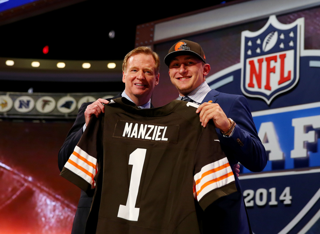 Johnny Manziel of the Texas A&M Aggies poses with NFL Commissioner Roger Goodell after he was picked #22 overall by the Cleveland Browns during the first round of the 2014 NFL Draft at Radio City Music Hall on May 8, 2014 in New York City.