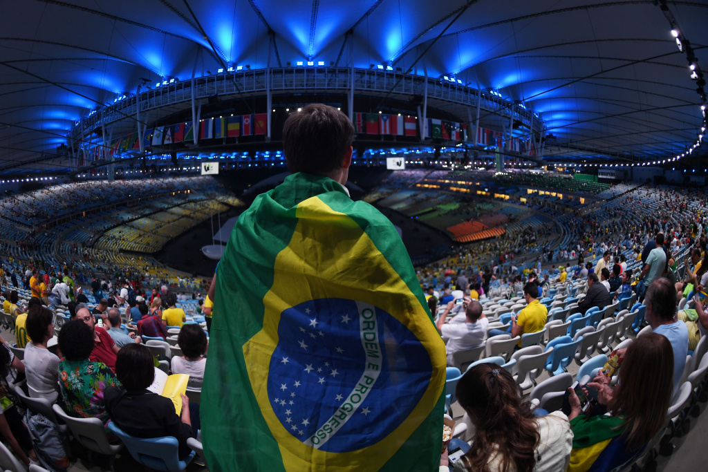 A spectator wrapped in a Brazilian flag prepares to watch the Aug. 5 opening ceremony of the 2016 Olympic Games at Maracanã Stadium in Rio de Janeiro.