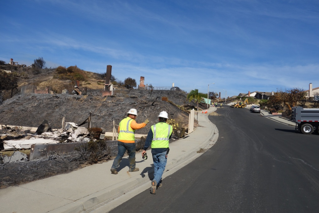 Contractors hike up a steep street in the Clearpoint neighborhood of Ventura, capping gas lines at homes that burned in the Thomas Fire.