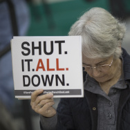 A woman holds a sign while attending a public hearing before the South Coast Air Quality Management District regarding a proposed stipulated abatement order to stop a nearby massive natural gas leak, on January 16, 2016 in Granada Hills, near Porter Ranch, California.