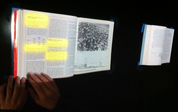 A projector above the books will be able to detect what page the reader is on, and highlight certain passages.