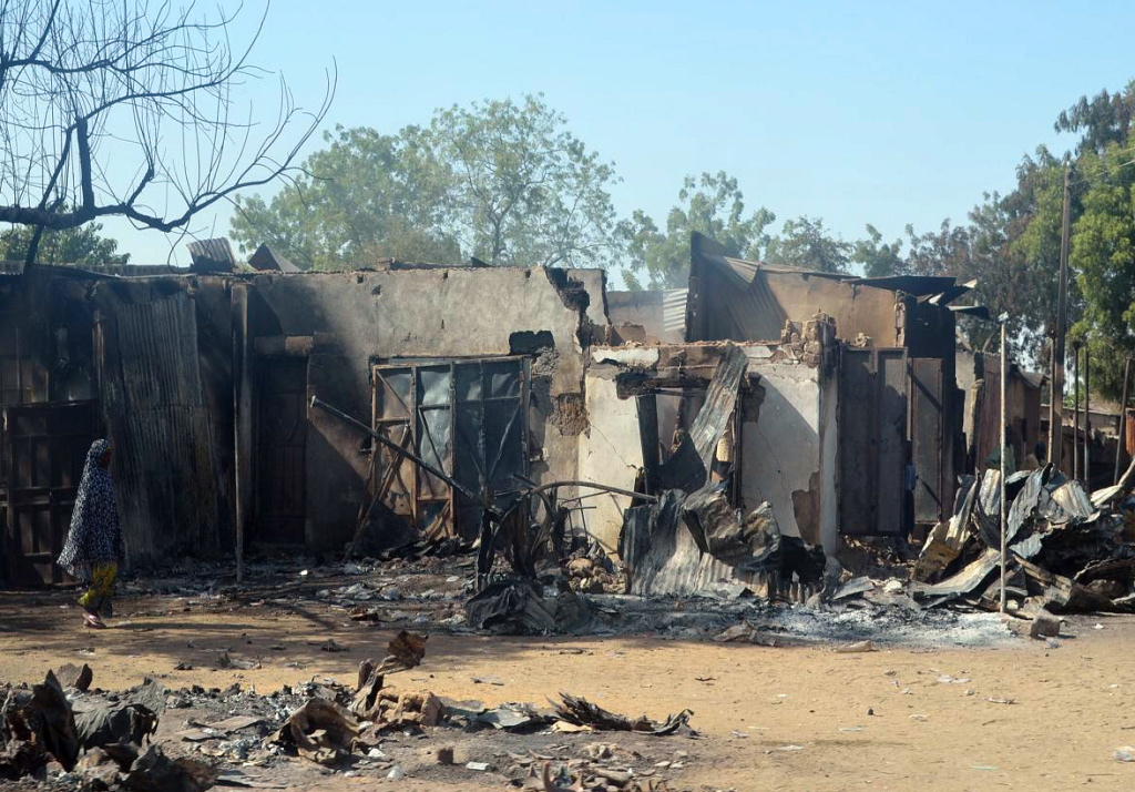 A woman walks past burnt houses after an attack by scores of Boko Haram Islamists on February 20, 2014 in the northeast Nigerian town of Bama. The extremist group is suspected to have have killed more than two dozen boys in an attack on a Nigerian school.