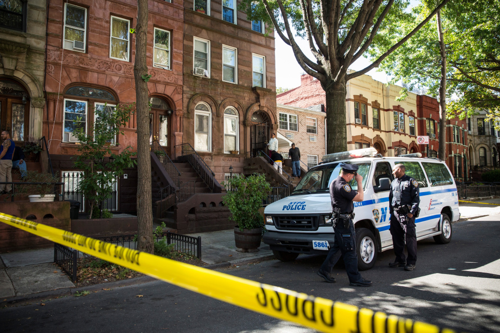 Policemen stand guard outside the home of Cathleen Alexis, the mother of Washington Navy Yard shooter Aaron Alexis, on Sept. 17, 2013 in the Bedford-Stuyvesant neighborhood of the Brooklyn borough of New York City.