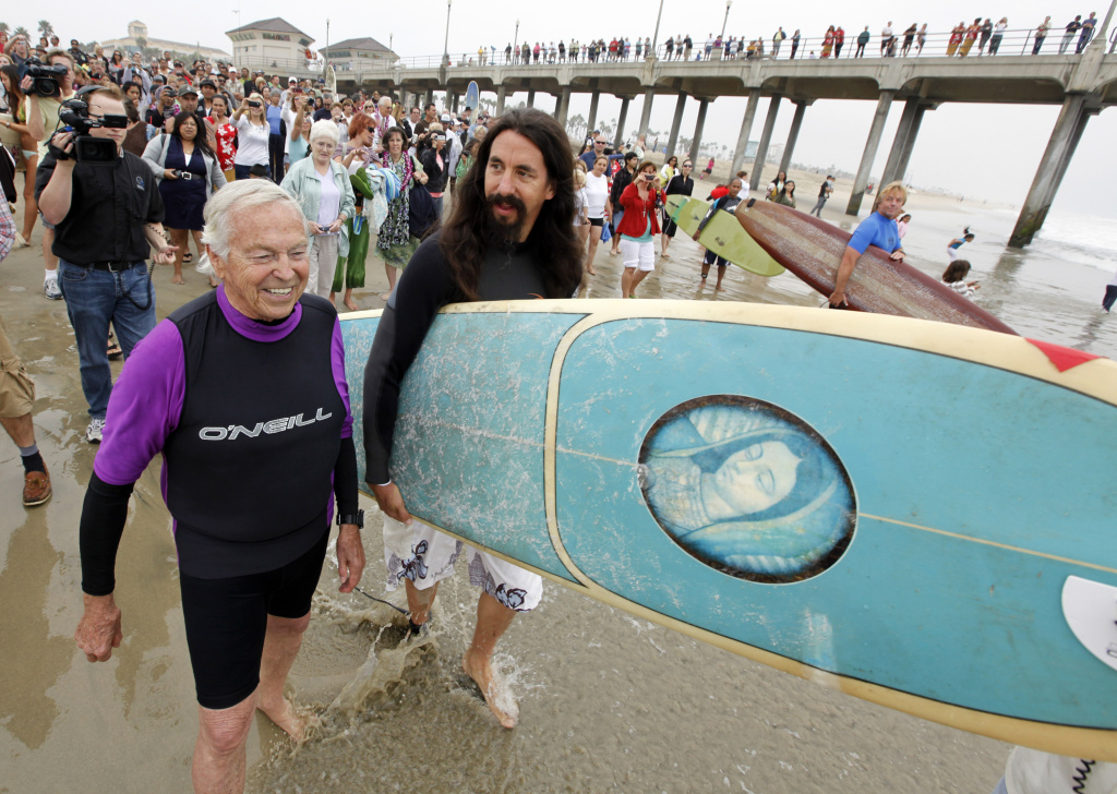 Rev. Christian Mondor, left, heads to the surf with Rev. Matt Munoz during the Blessing of the Waves ceremony at the pier in Huntington Beach on Oct. 3, 2010.