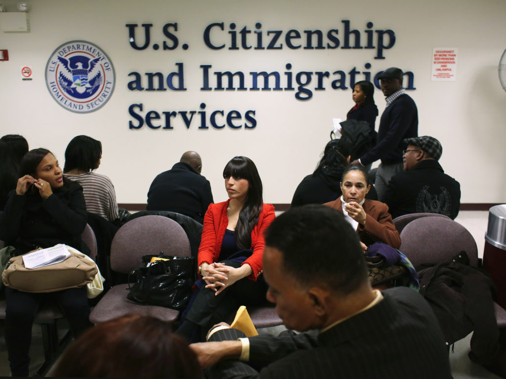 Immigrants wait for their citizenship interviews at a U.S. Citizenship and Immigration Services office in New York. They must pass a two-part test on English and civics.