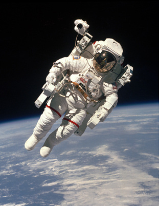 An astronaut floats in outer space.