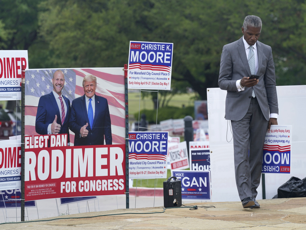 Volunteer Al Green looks at his phone as he takes a break from holding a sign supporting his candidate in a local election outside an early voting location Tuesday, April 27, 2021, in Mansfield, Texas.