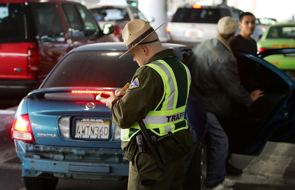 A parking enforcement officer gives a citation to a driver who stopped in the wrong place to pick up arriving travelers at Los Angeles International Airport (LAX) on November 23, 2004 in Los Angeles, California.