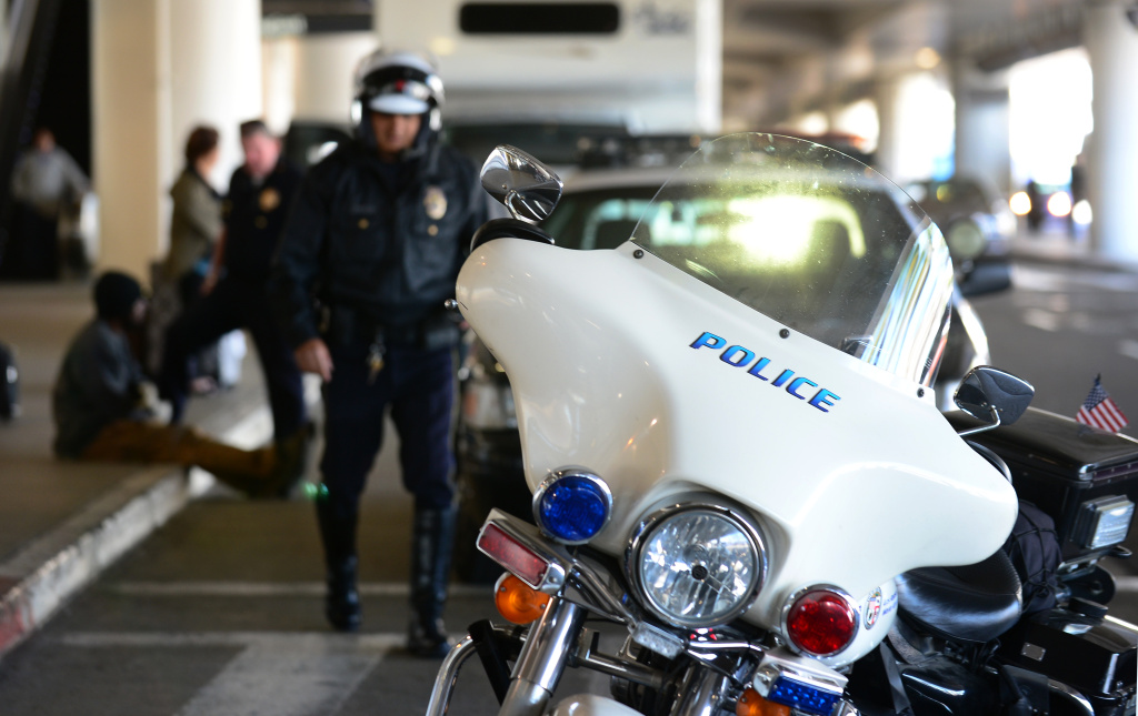 File: A motorcycle policeman returns to his bike after checking with police officers questioning a man curbside at Los Angeles International Airport amid a heightened security alert on April 16, 2013.