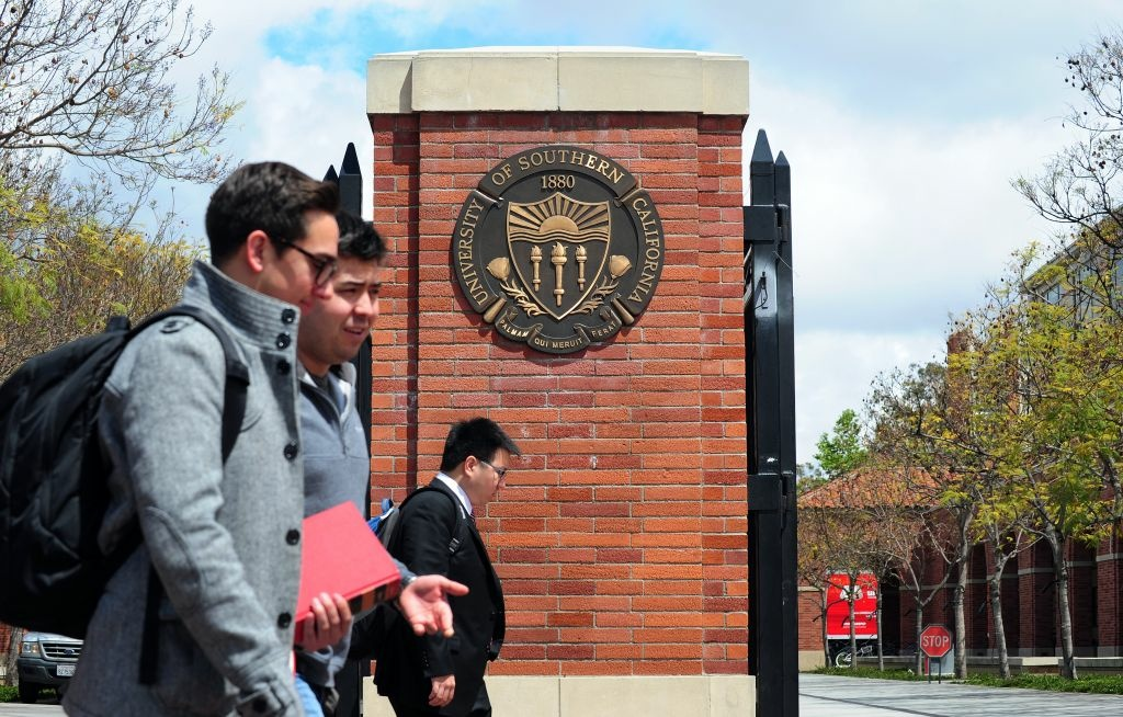 Students walk past an entrance to the University of Southern California (USC) in Los Angeles on April 11, 2012 in California.