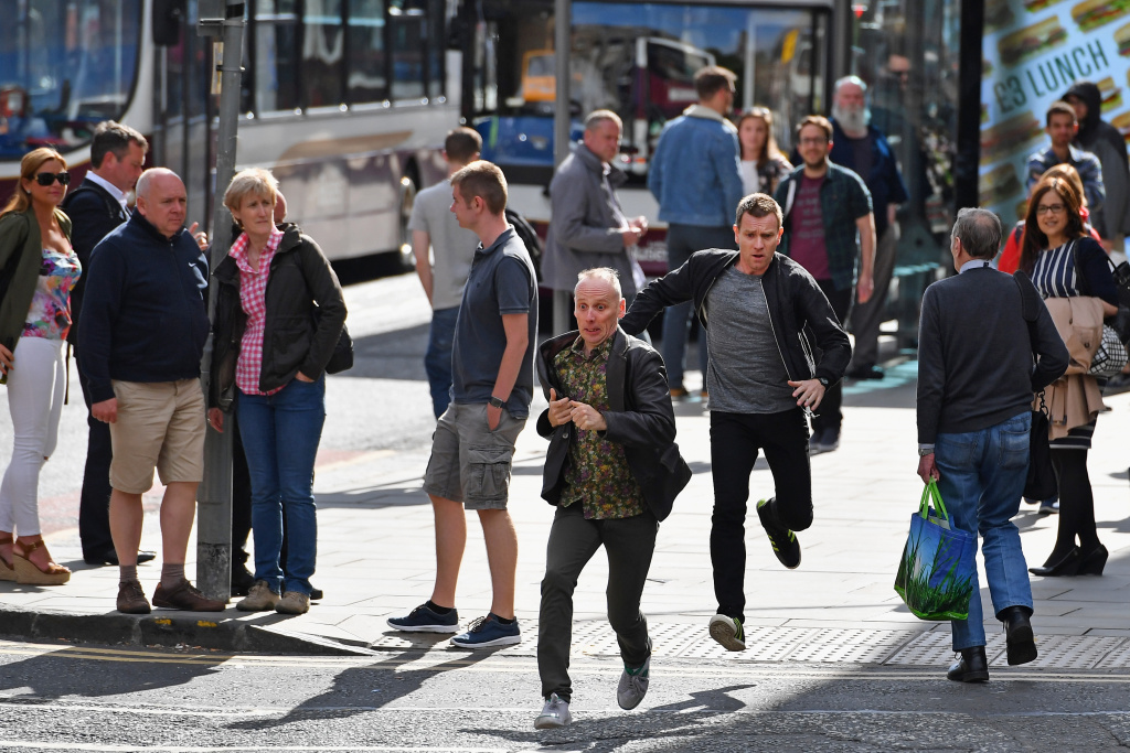 Actors Ewan McGregor and Ewan Bremner run on the set of the Trainspotting film sequel on Princess Street on July 13, 2016 in Edinburgh, Scotland.