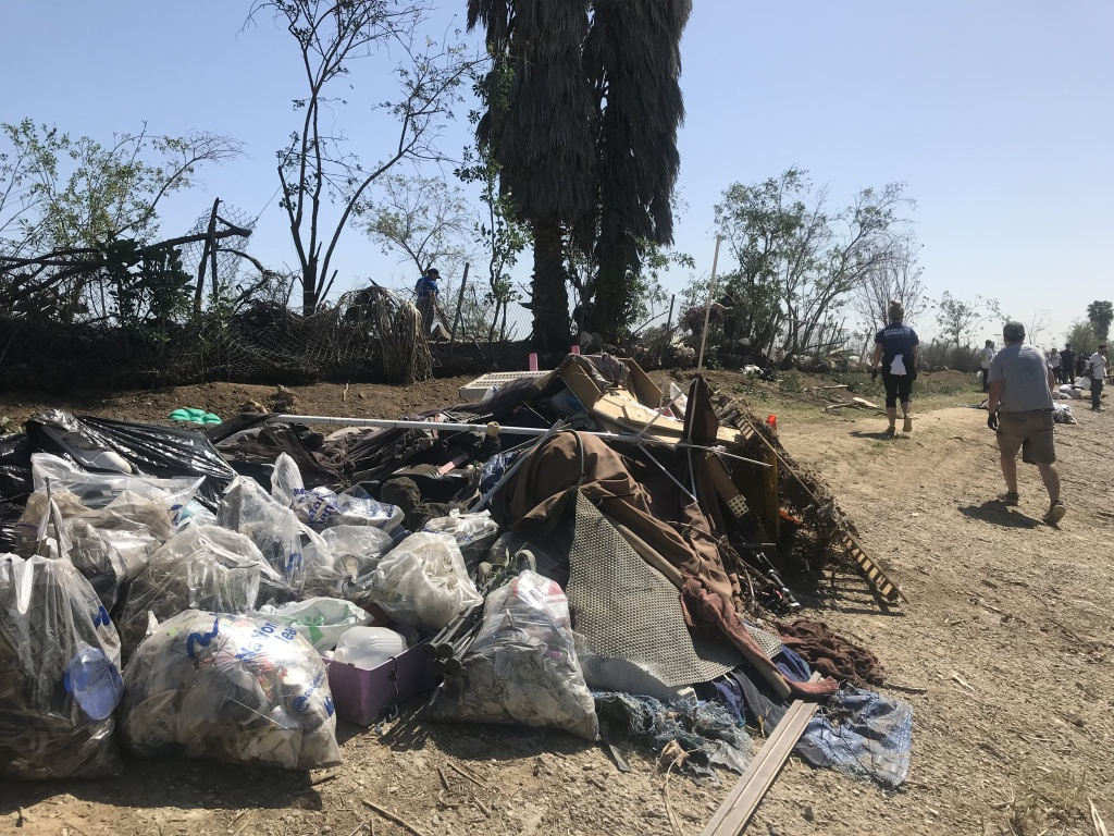Piles and piles of garbage were collected from an abandoned homeless camp on the riverbank. Photo credit: Audrey Alden