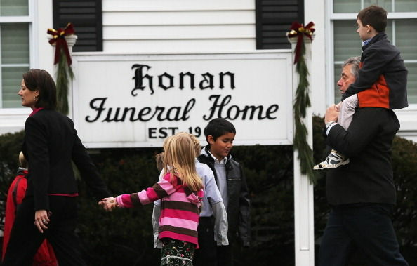 People walk to enter Honan Funeral Home before the funeral for 6-year-old Jack Pinto on December 17, 2012 in Newtown Connecticut. Pinto was one of the 20 students killed in the Sandy Hook Elementary School mass shooting.