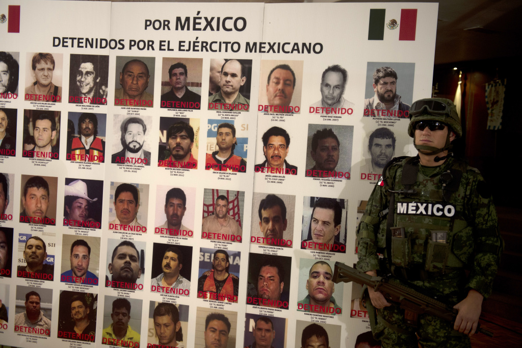 A Mexican army soldier stands guard beside a placard with pictures of alleged drug cartels members already arrested during the presentation to the press on May 21, 2012 in Mexico City.