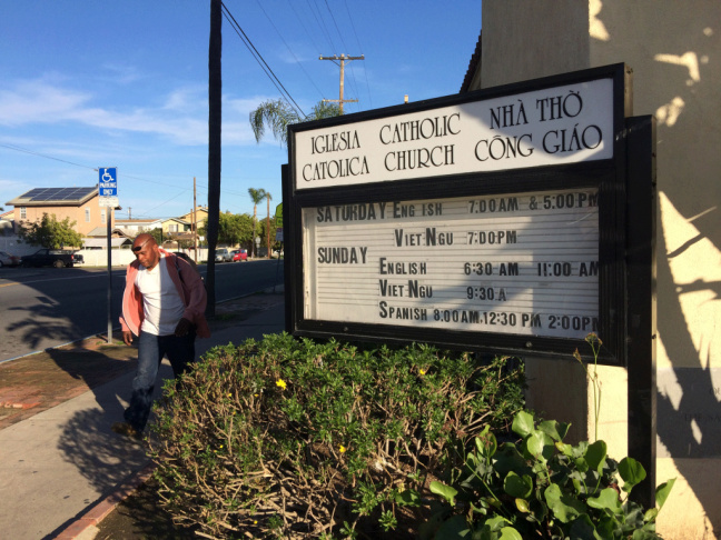 A man walks past Our Lady of the Sacred Heart in the Teralta West neighborhood of City Heights, Jan. 20, 2016. The Catholic church offers services in English, Spanish and Vietnamese.