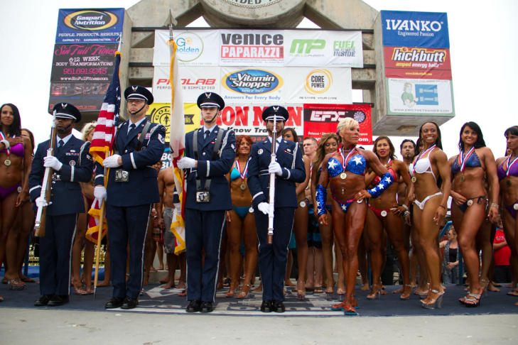 Venice Beach, CA: July 4, 2012 - Contestants on stage with members of the U.S. Airforce Honor Guard to sing the National Anthem during the Venice Beach body building pageant on the Venice Beach Boardwalk.  (Julie Platner/KPCC)