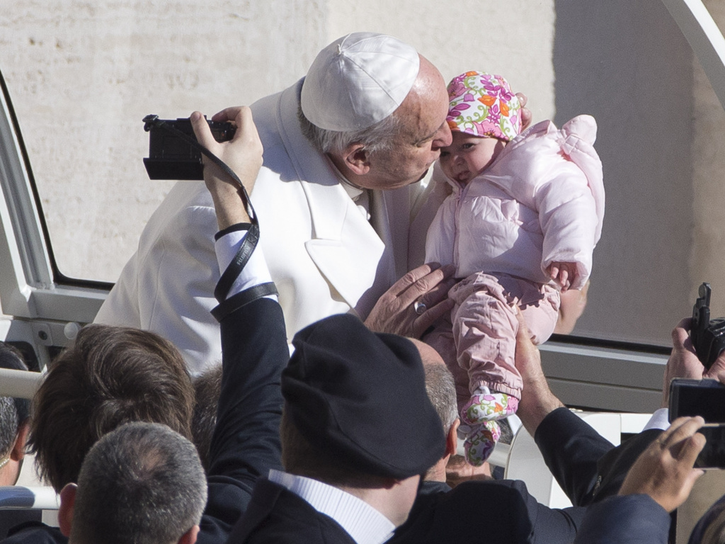 Pope Francis kisses a baby as he arrives for his weekly general audience in St. Peter's Square, at the Vatican, on Wednesday.