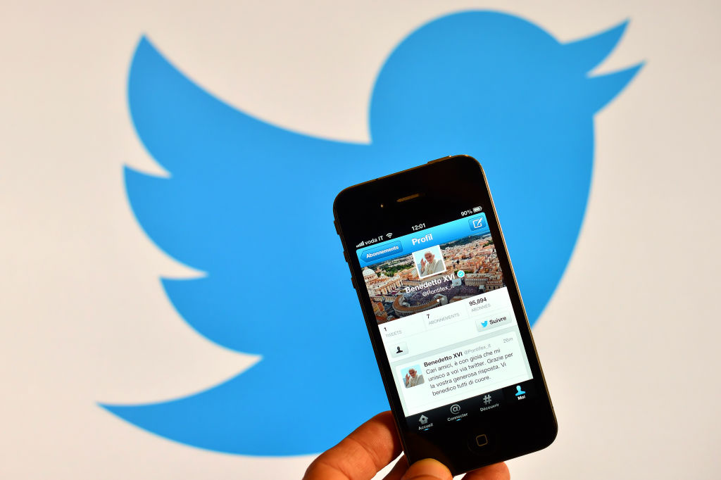 A smartphone showing the first twitter message of Pope Benedict XVI in Italian is held in front of a computer showing the logo of Twitter on December 12, 2012 in Rome.