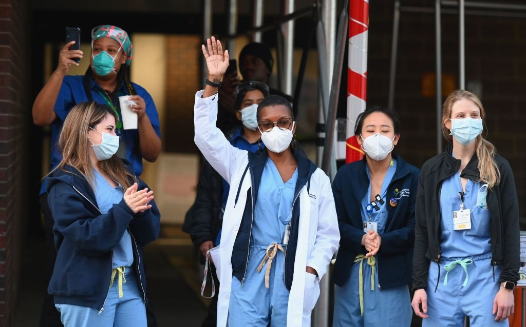 Brooklyn Hospital Center personnel wave and clap outside the Brooklyn Hospital Center at 7pm on April 15, 2020 in New York City.