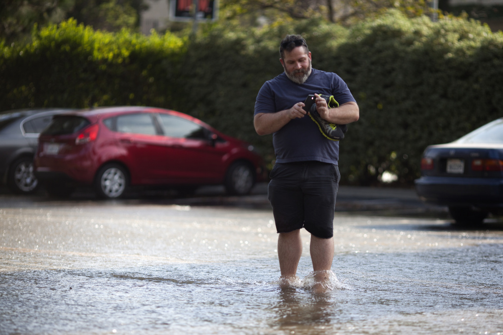 Rob Strotman, who works in the IT department for the School of Arts and Architecture takes a video with his cellphone of the water flowing on campus from a ruptured water main on Sunset Boulevard.