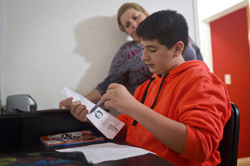 Twelve-year-old Luis Dauila, a student at Camino Nuevo Charter School, checks over his homework on Greek gods.