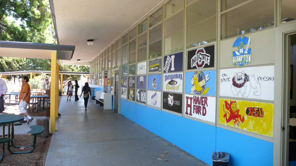 Students paint signs with the names and logos of colleges that former classmates now attend. Environmental Charter High School requires that each of its students get accepted into a traditional four-year college or university in order to graduate.
