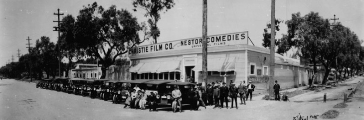 The first motion picture studio in Hollywood was built by David Horsley for Christie Film Co. Automobiles are lined up at Sunset Blvd., with Gower Street at right. The sign above the building reads