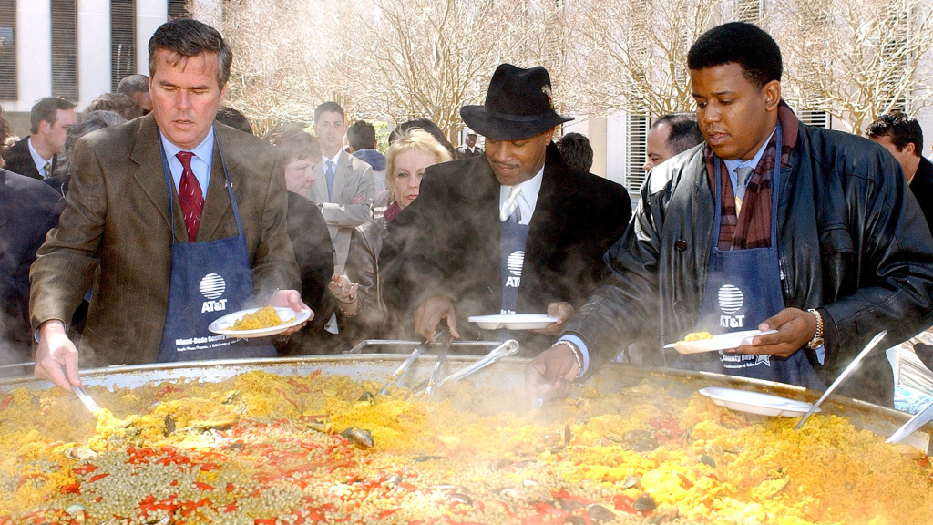 Former Gov. Jeb Bush (left) serves helpings of paella to guests attending the Miami-Dade Day festivities in 2002, with former state Rep. Gary Siplin (center) and former U.S. Sen. Kendrick Meek.