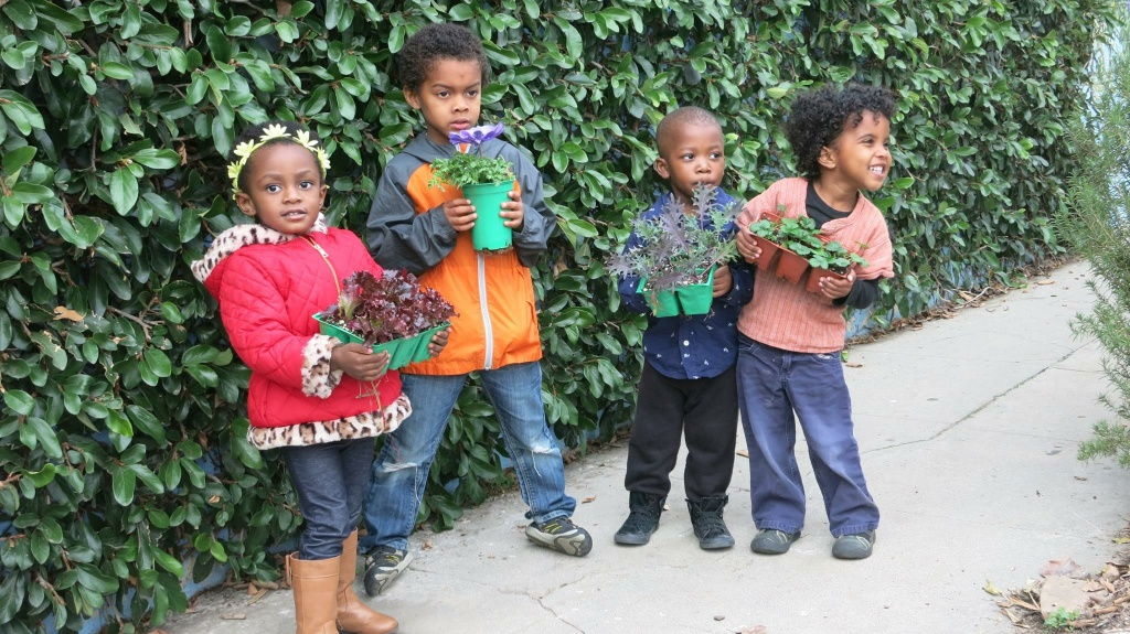 Children don pots of plants in Ron Finley's urban garden in South Central L.A.
