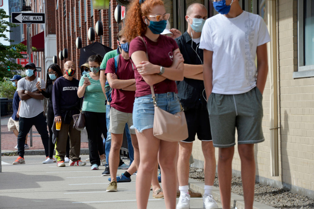 People wait in line to be tested for Covid-19 just a few hundred feet to where a polling station is based in Chinatown during the Massachusetts State Primary on September 1, 2020 in Boston, Massachusetts.