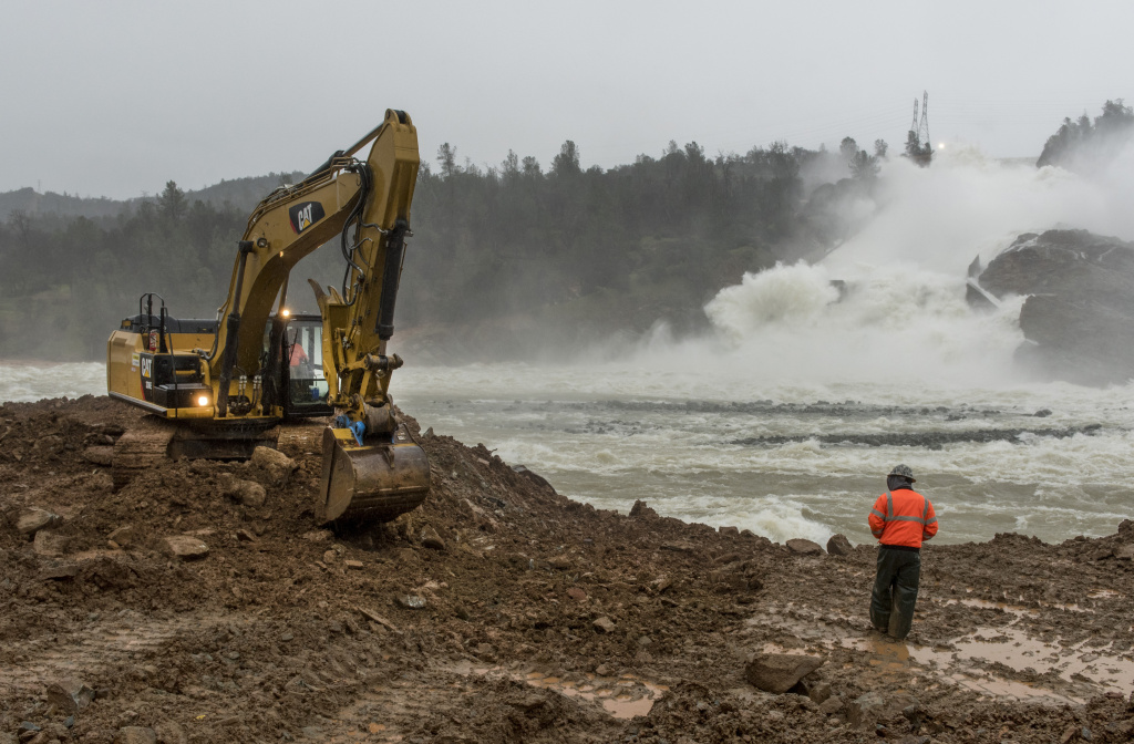 Work continues along the riverbank across the damaged spillway at Oroville Dam. Workers are shoring up the bank to allow heavy equipment to remove sediment and debris from the diversion pool on February 17, 2017 in Oroville, California