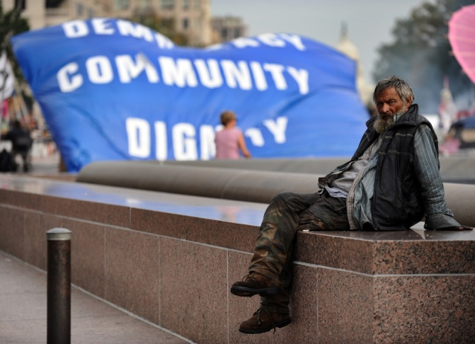 A homeless man sits near a banner during