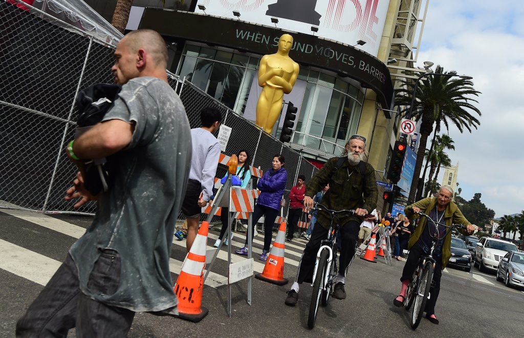 Hollywood Boulevard at Highland Avenue in Hollywood, California is closed off to the public as pedestrians pass a large statue of the Oscar in this February 21, 2015 file photo. The city has already begun to close streets and enforce parking restrictions as crews prepare for the 2018 Academy Awards show.
