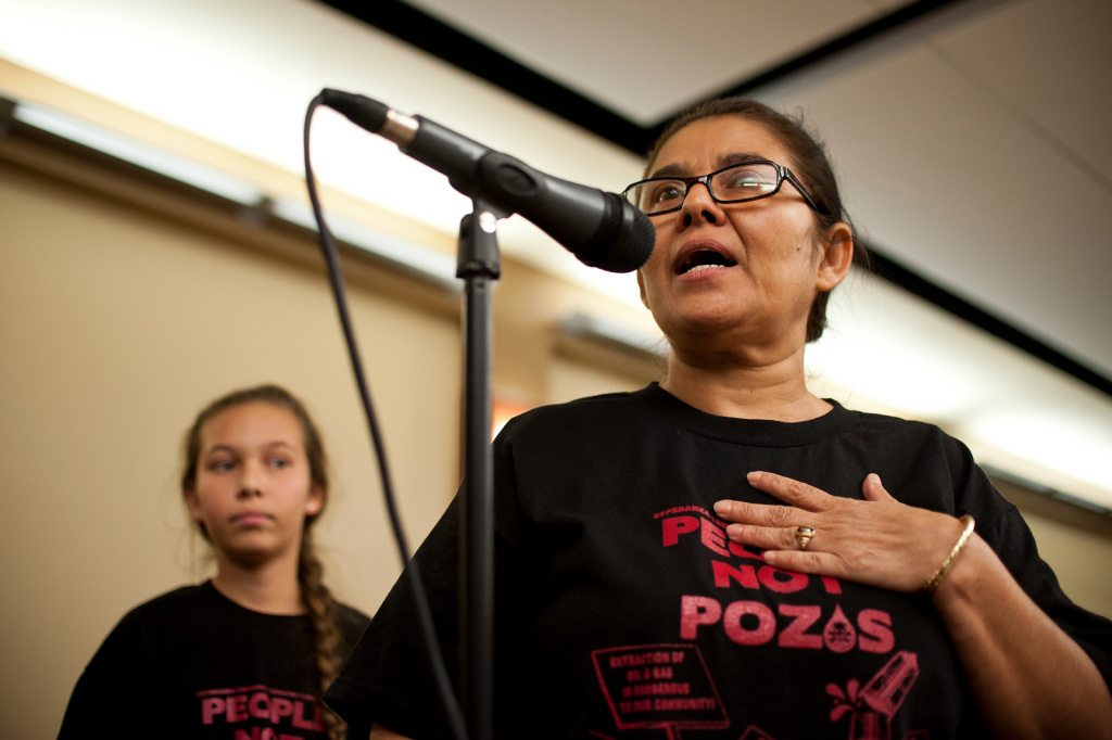 Resident Monic Uriarte of the Esperanza Community Housing Corporation speaks with her daughter, left, during a 2013 town hall meeting hosted by South Coast Air Quality Management District discussing findings from air monitoring and enforcement efforts related to AllenCo Energy, Inc. in the University Park. The company just settled a lawsuit with the city of Los Angeles.