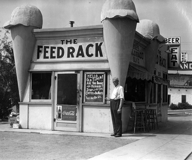 Originally built as an ice cream parlor with an oversized ice cream cone at each corner, the building became the Feed Rack restaurant during the Depression. Notice the sign: