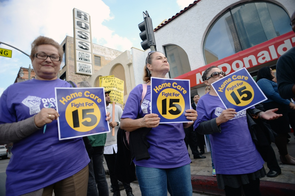 Home healthcare workers join fast food workers and their supporter at a rally and march to demand an increase of the minimum wage to 15USD per hour, in Los Angeles on December 4, 2014.